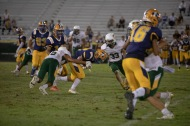 Colonist Adam Luna (22) bulls into the Vaquero's secondary for good yardage during Friday's game at Glover Field.